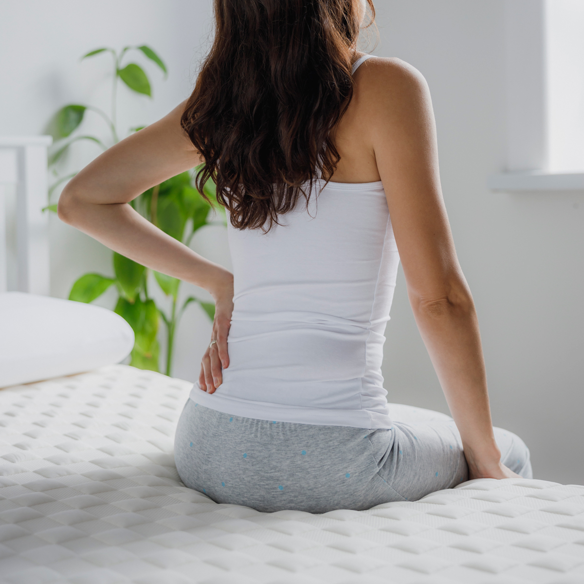 woman with back pain sitting on a bed