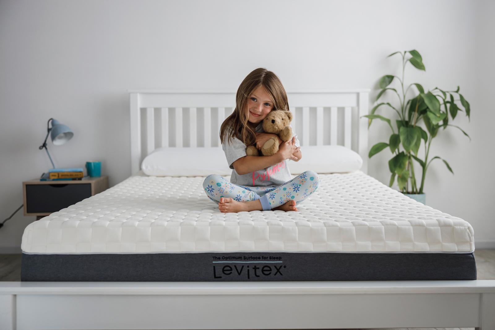 girl sitting on back pain mattress